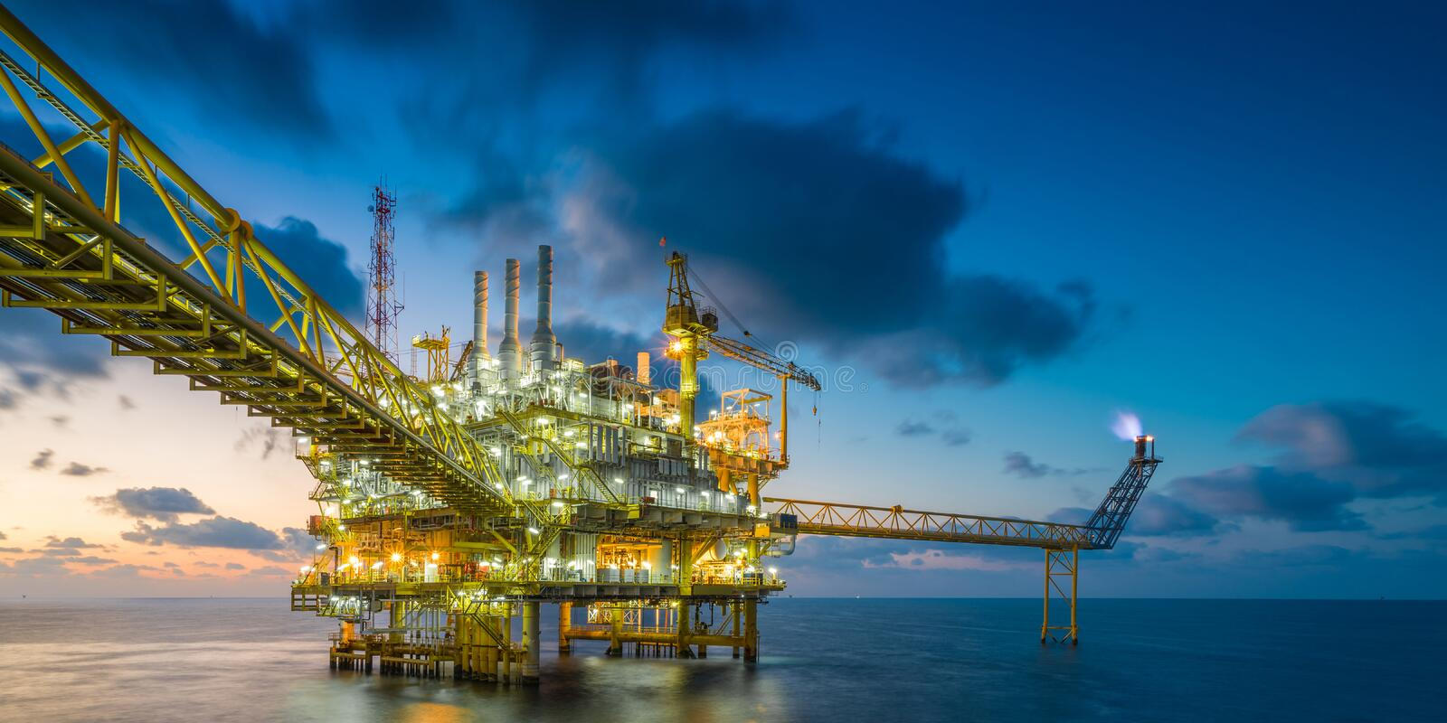 Offshore oil and gas central processing platform in sun set where produced raw gases and treat then sent to onshore refinery. Oil and gas central processing stock image