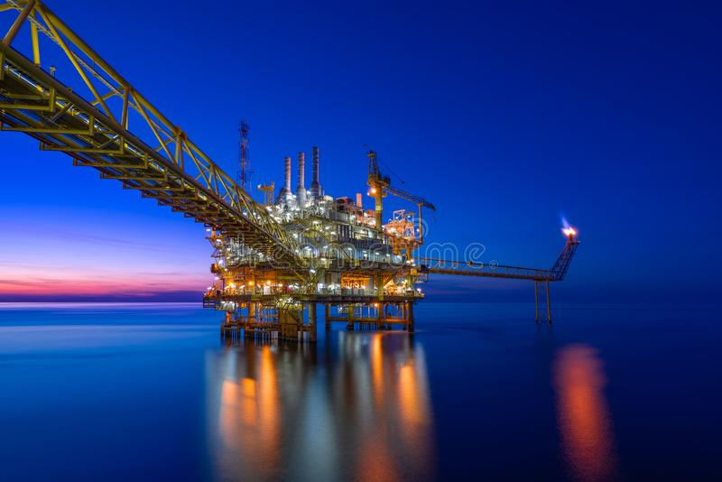 Offshore oil and gas central processing platform in sunset, petroleum business for worldwide energy.  stock photos