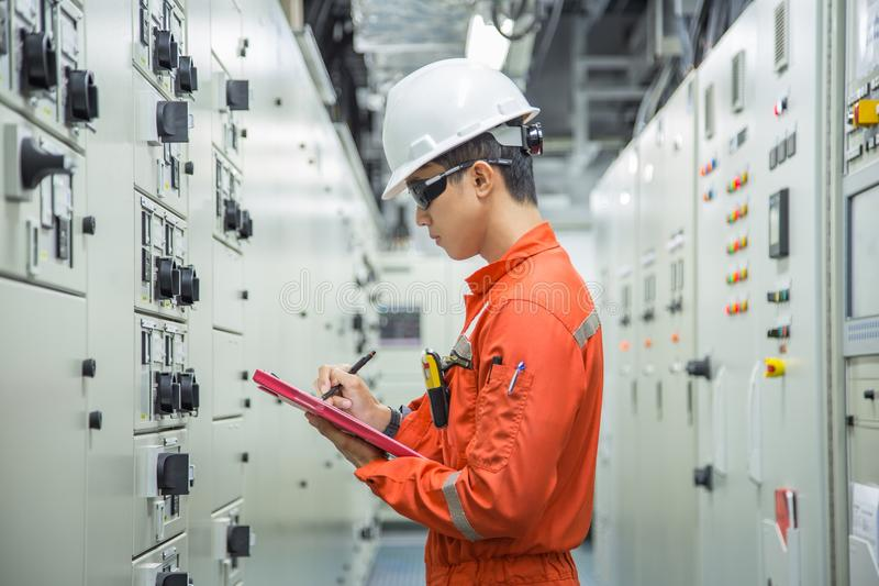 Electrical and Instrument technician logging data in electrical switch gear room. royalty free stock photo