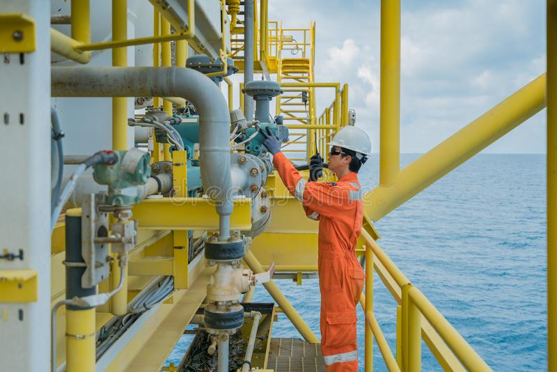 Offshore oil and gas worker operating gas oil flow meter. Offshore oil and gas worker operating touch screen of gas flow meter coriolis type to reading and royalty free stock photos