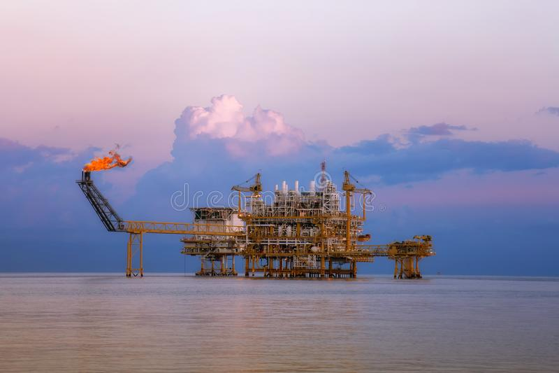Offshore oil and rig platform in sunset or sunrise time. Construction of production process in the sea royalty free stock photos