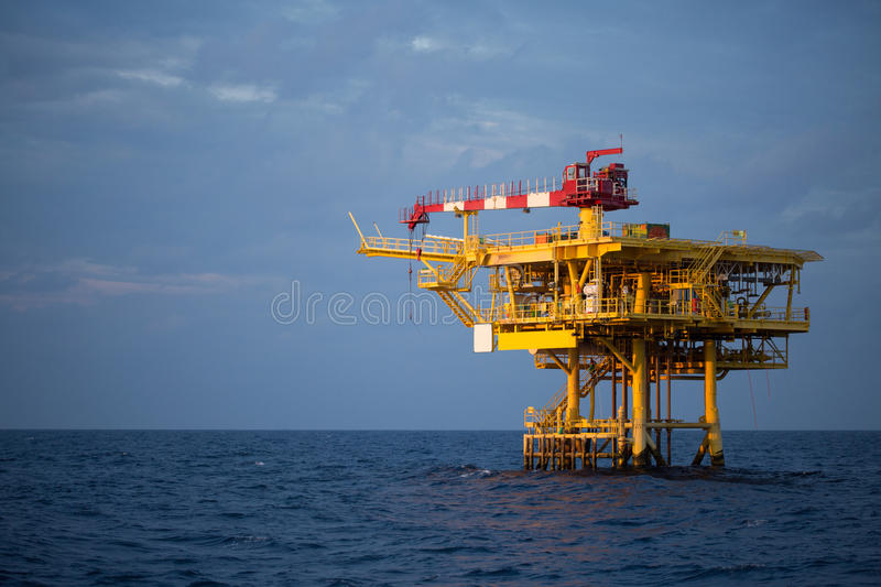 Offshore oil and rig platform in sunset or sunrise time. Construction of production process in the sea. Power energy of the world.  royalty free stock photo