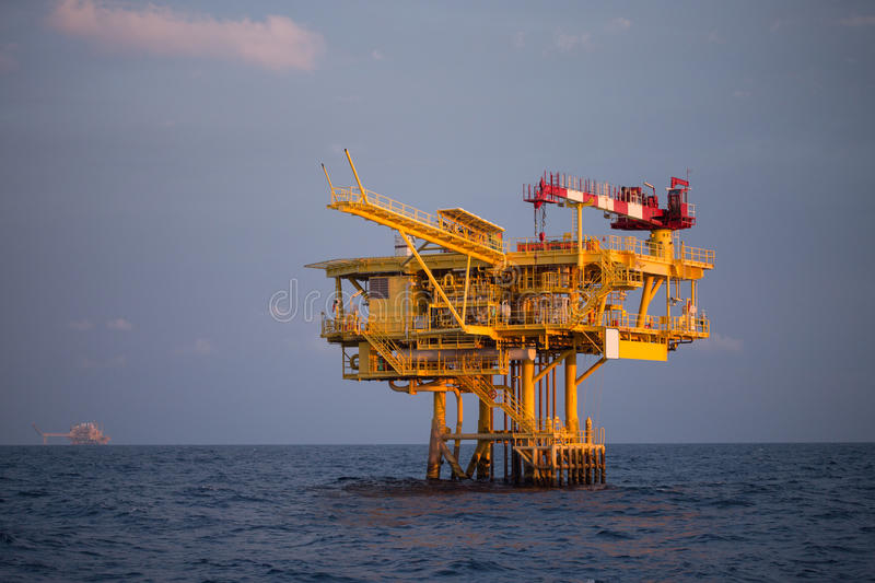 Offshore oil and rig platform in sunset or sunrise time. Construction of production process in the sea. Power energy of the world.  royalty free stock images