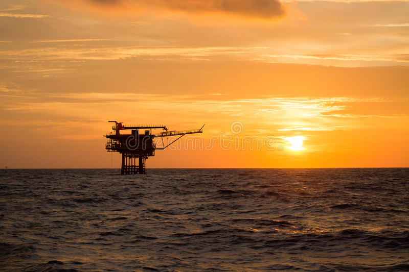 Offshore oil and rig platform in sunset or sunrise time. Construction of production process in the sea. Power energy of the world.  stock photos