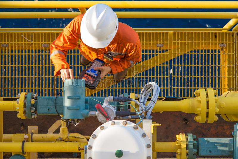 Offshore oil rig worker calibrating coriolis digital flow meter at processing platform. Offshore oil rig worker calibrating coriolis digital flow meter by using royalty free stock photography