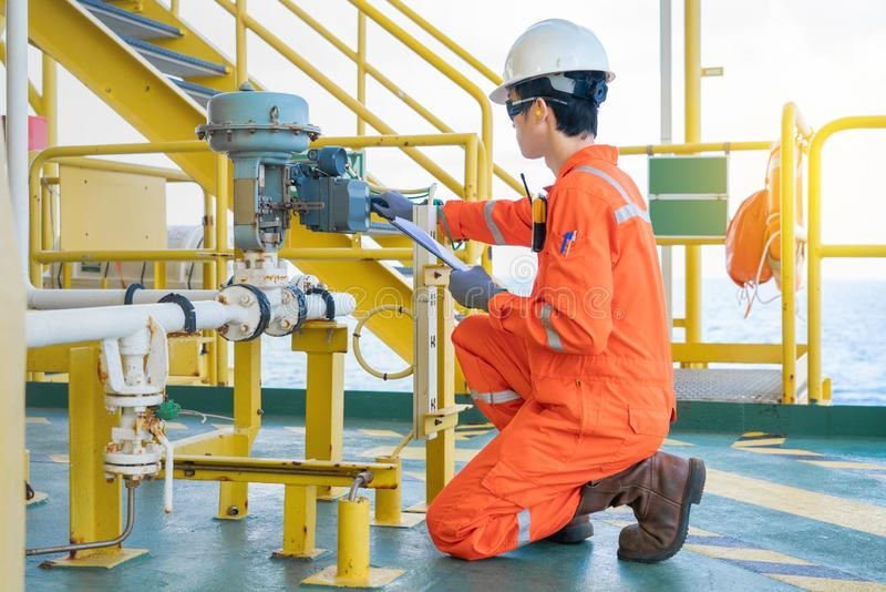 Offshore oil rig worker checking actuated control valve and adjusting pressure regulator on gas processing platform.. royalty free stock photo