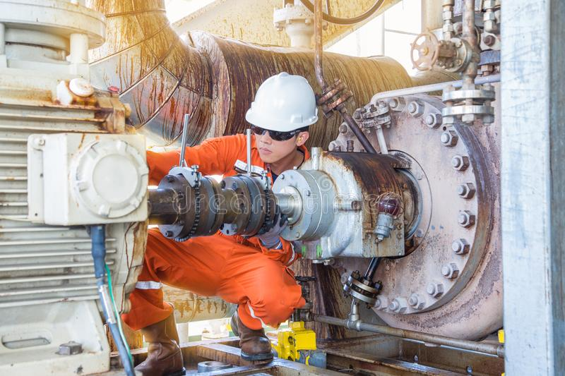Offshore Oil Rig worker, Mechanical technician inspecting oil centrifugal pump. Alignment to prevent vibration which damage bearing and mechanical seal systems stock photo