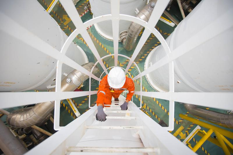 Offshore oil rig workor climb up to gas processing platform. Process engineer climb up to the top of gas dehydration vessel to inspect and check abnormal royalty free stock images