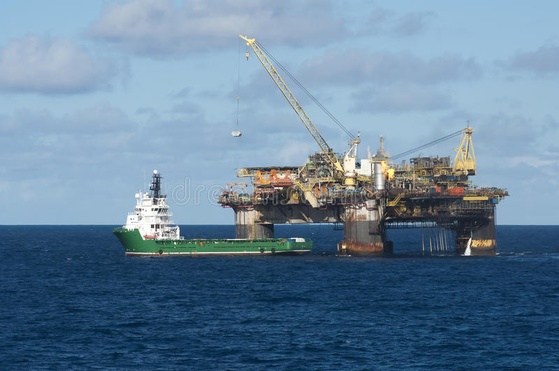 Offshore operation. Crane operation for container transfering from an oil rig to a supply vessel in offshore area stock photo