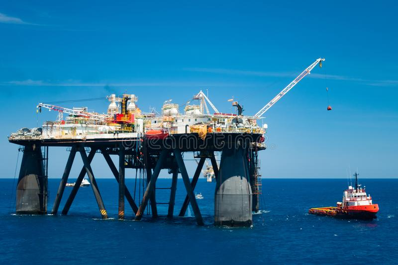 Offshore operation with oil rig and vessel. Cargo transfer operation on oil rig to a supply vessel in offshore area stock images