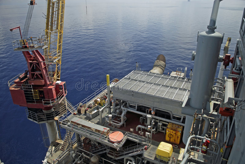 Offshore Platform. A view from the derrick of a section of an offshore platform's compressor area and crane royalty free stock image