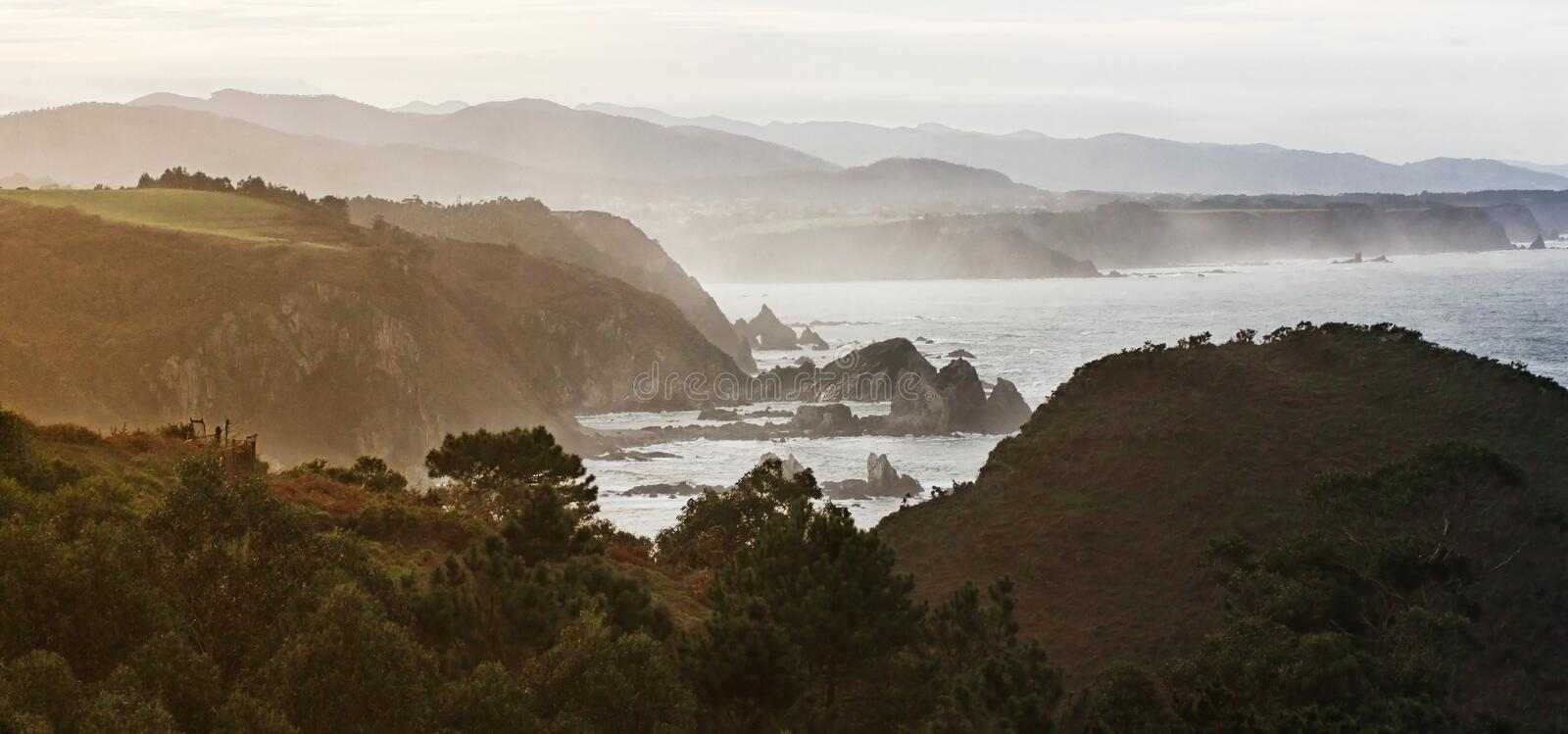 Offshore rocks and coastline in foggy evening royalty free stock photos