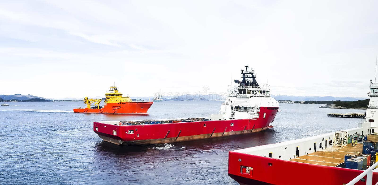 Offshore ships in Norwegian fiords arriving for resupply and ref. Modern norwegian ships arriving to port for loading new supplies, provision and bunkers royalty free stock images