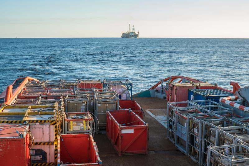 Offshore supply boat delivers cargo to oil rig platform royalty free stock image