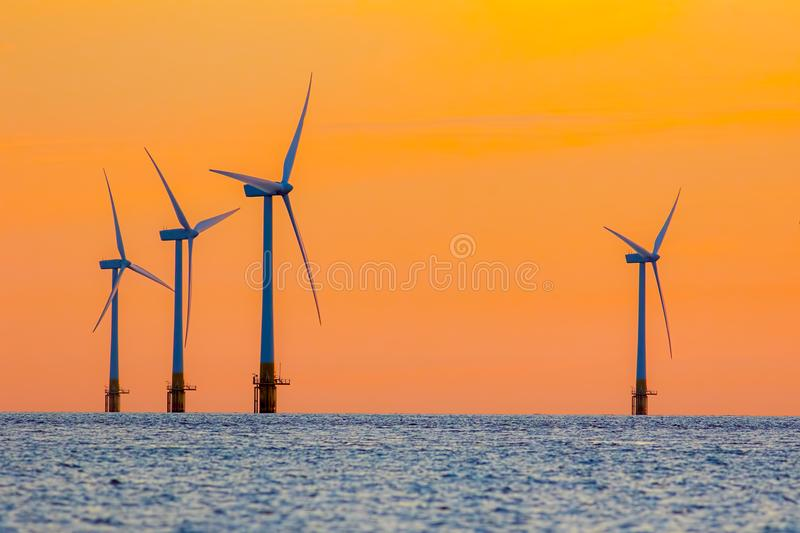 Offshore wind farm energy turbines at dawn. Surreal but natural stock images