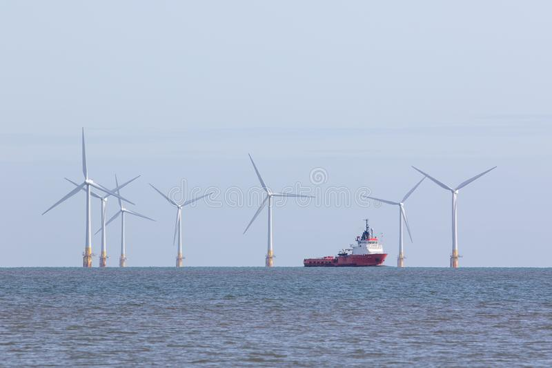 Offshore wind farm turbines with maintenance supply vessel ship stock photos