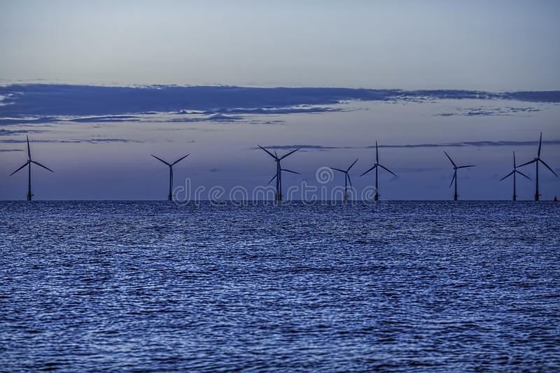Offshore wind farm turbines between night and day royalty free stock photography