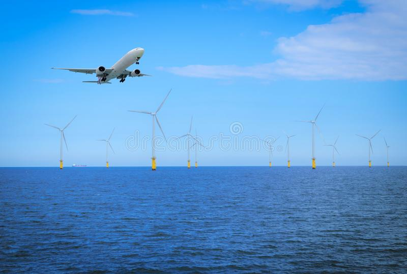 Offshore Wind Turbine with plane fly in a Wind farm under construction off coast of England. stock photography