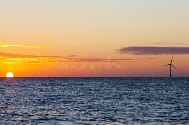 Offshore wind turbine at sunrise stock photo
