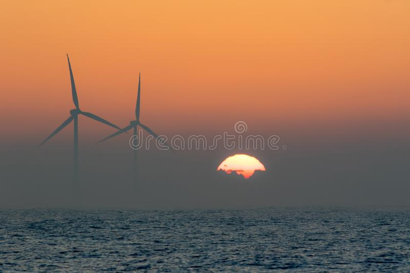 Offshore wind turbines. Misty morning sea sunrise. Tropical back. Offshore wind turbines. Misty morning sea sunrise. Tropical dawn travel background landscape royalty free stock images