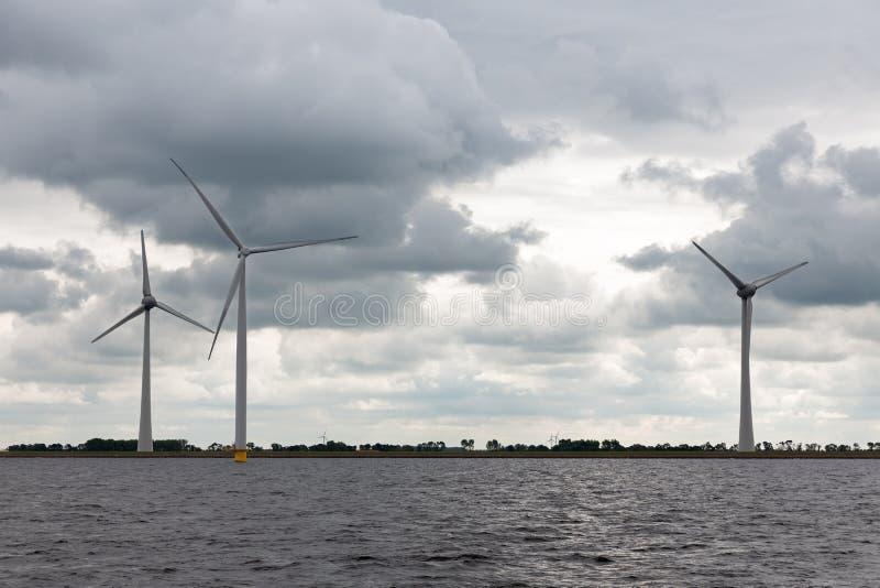 Offshore-windfarm nahe niederländischer Küste mit bewölktem Himmel stockfoto