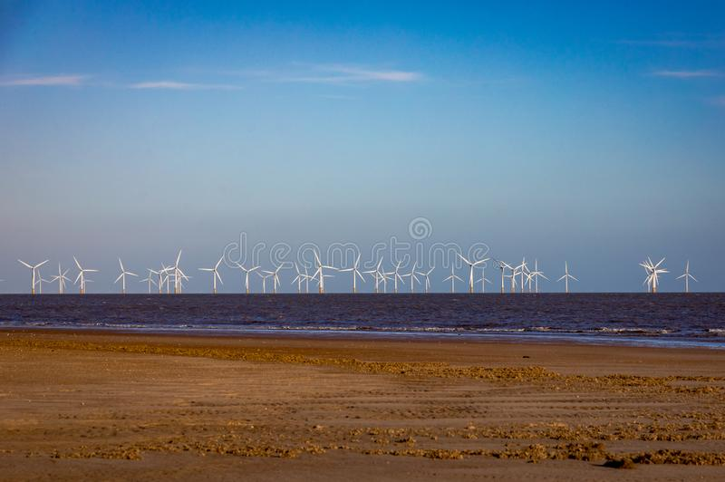 Offshore windfarm off the coast of Lincolnshire, UK. 16x9 view of a large windfarm off the coast of Linconshire. The view includes the beach in the foreground stock photo