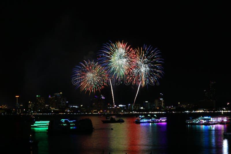 offuschi i fuochi d'artificio rossi verdi dell'oro sulla spiaggia ed il colore della riflessione sulla superficie dell'acqua fotografia stock