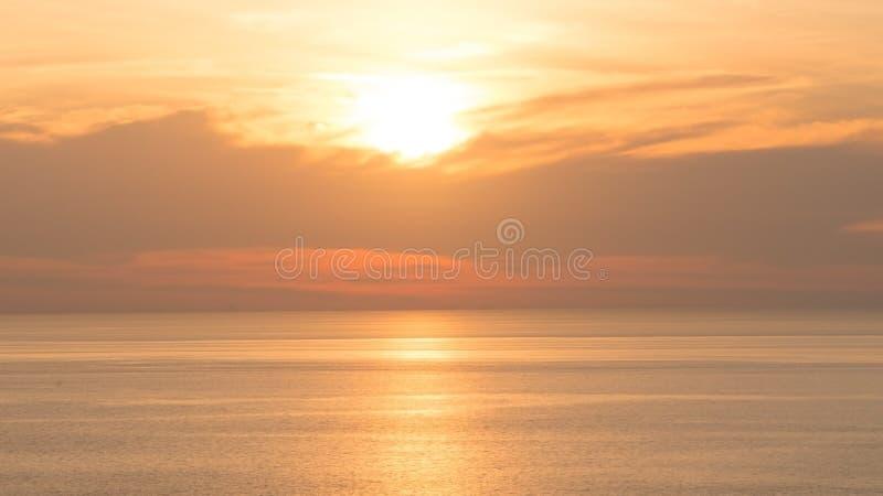 Offuschi il bello cielo arancio molle sopra il mare Tramonto nel fondo Cielo arancione astratto Cielo dorato drammatico al backgr fotografia stock