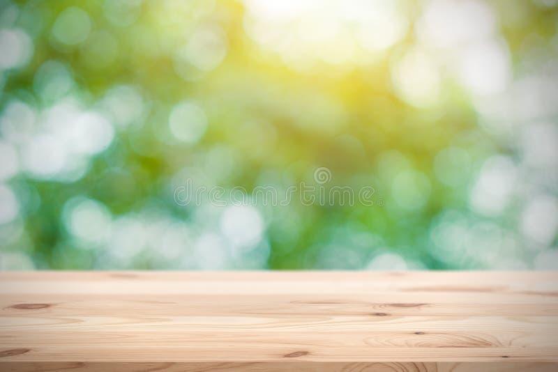 Offuschi il verde con lo spazio di legno della tavola per l'esposizione dei prodotti immagini stock libere da diritti