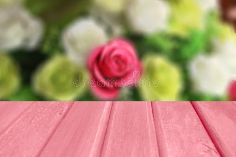 Offuschi l'immagine di sfondo delle rose di colore e del pavimento di legno vuoto, per il montaggio e l'esposizione, in biglietto fotografia stock