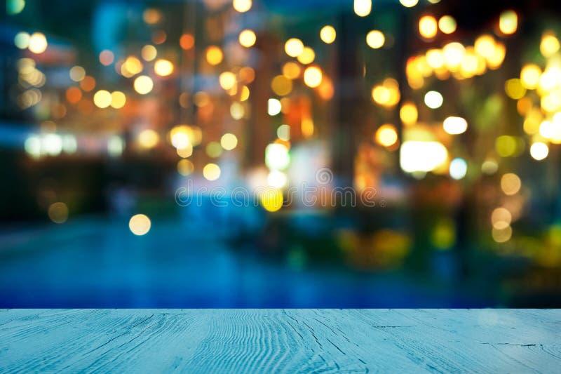 Offuschi la luce della barra o del pub accanto al partito dell'estate della piscina dell'acqua blu alla notte con la cima del fon fotografia stock libera da diritti