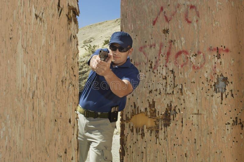Oficial Aiming Hand Gun en la gama de leña fotos de archivo