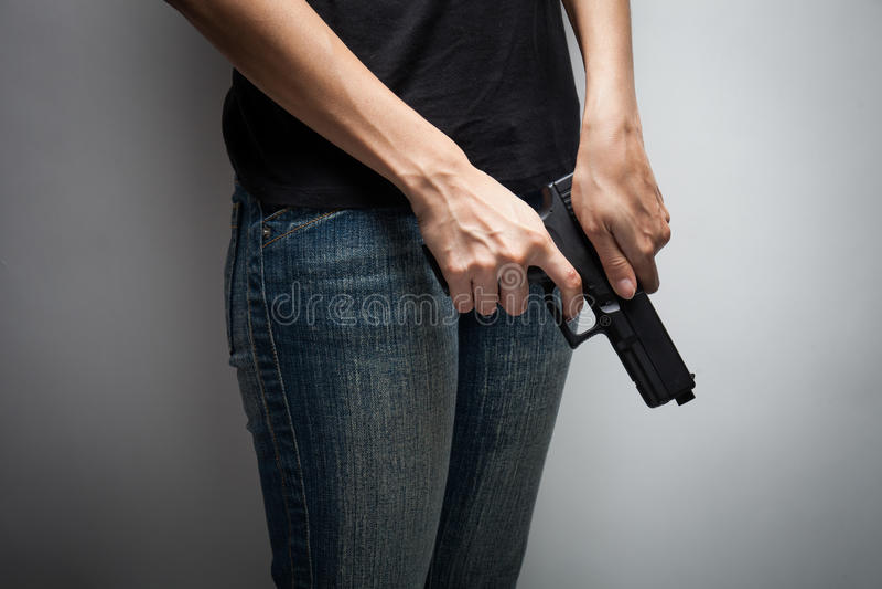 Oficial Concealing Weapon da menina imagem de stock