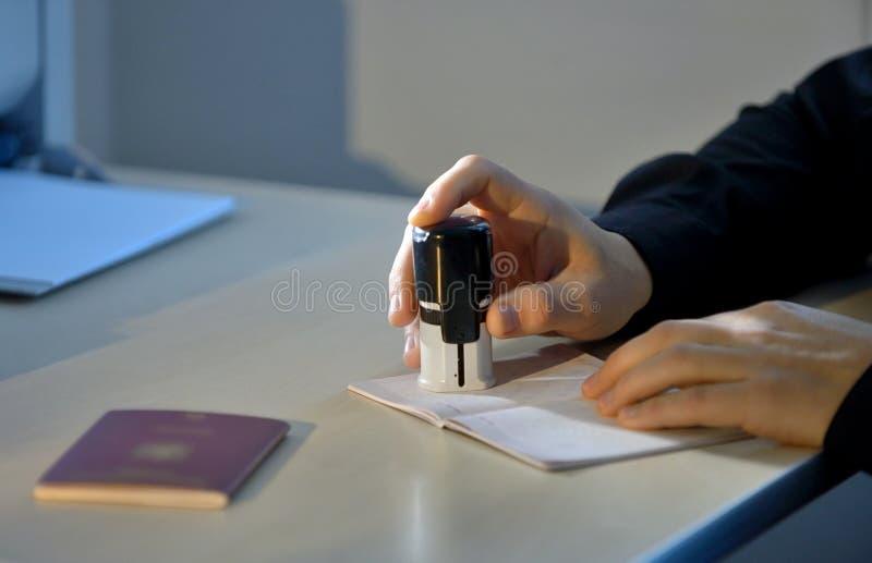 Oficial de aduanas Stamping un pasaporte fotos de archivo libres de regalías