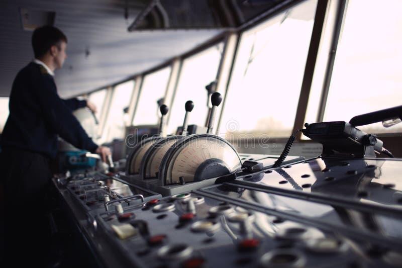 Oficial de la navegación que conduce la nave en el río imagen de archivo