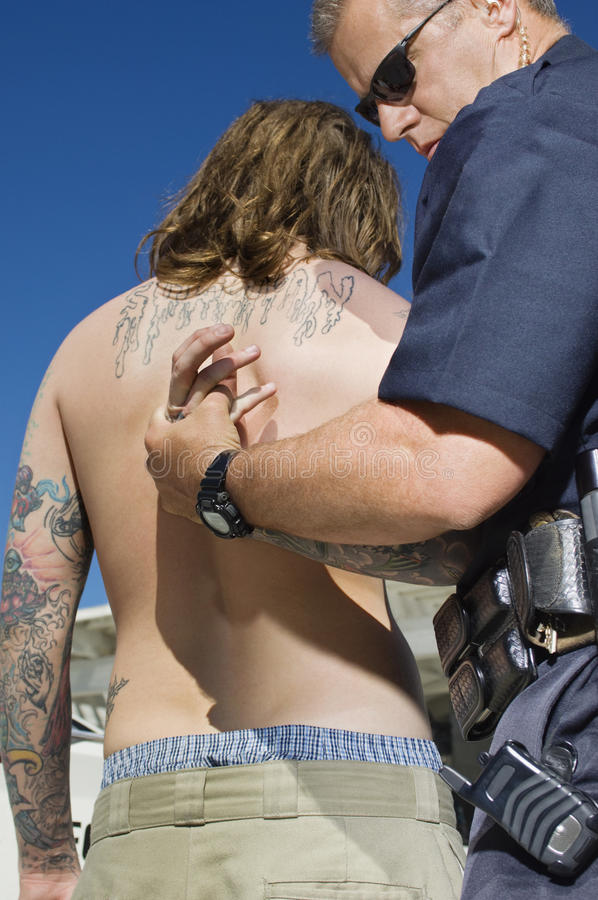 Oficial de policía Arresting Young Man foto de archivo