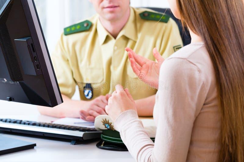 Oficial de policía en el departamento que registra denuncia imagen de archivo