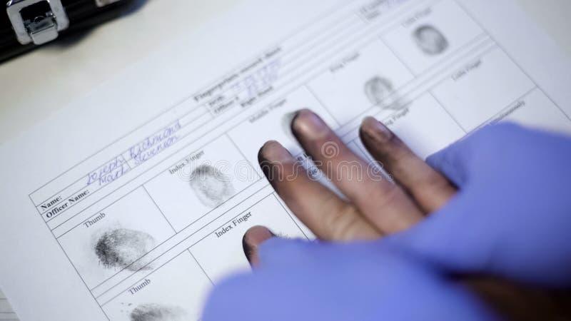 Oficial de policía en los guantes del examen que toman huellas dactilares del sospechoso, primer de las manos fotografía de archivo