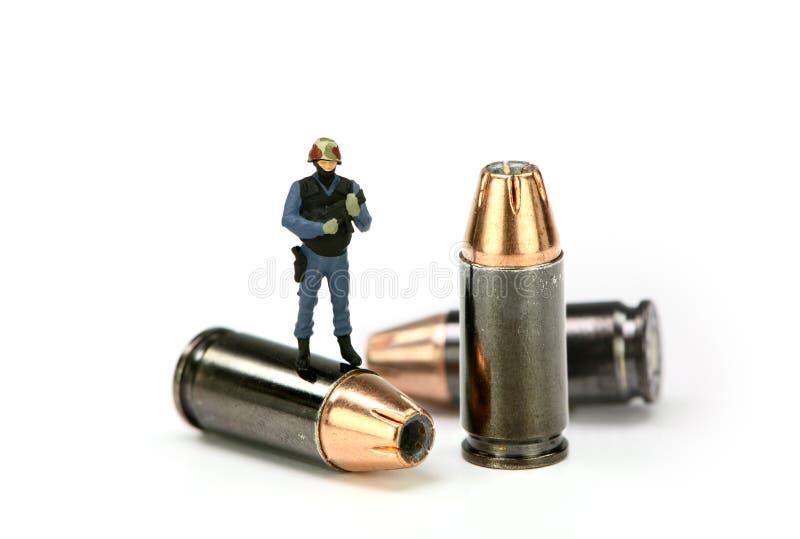 Oficial de policía miniatura en engranaje del GOLPE VIOLENTO en un punto negro imágenes de archivo libres de regalías