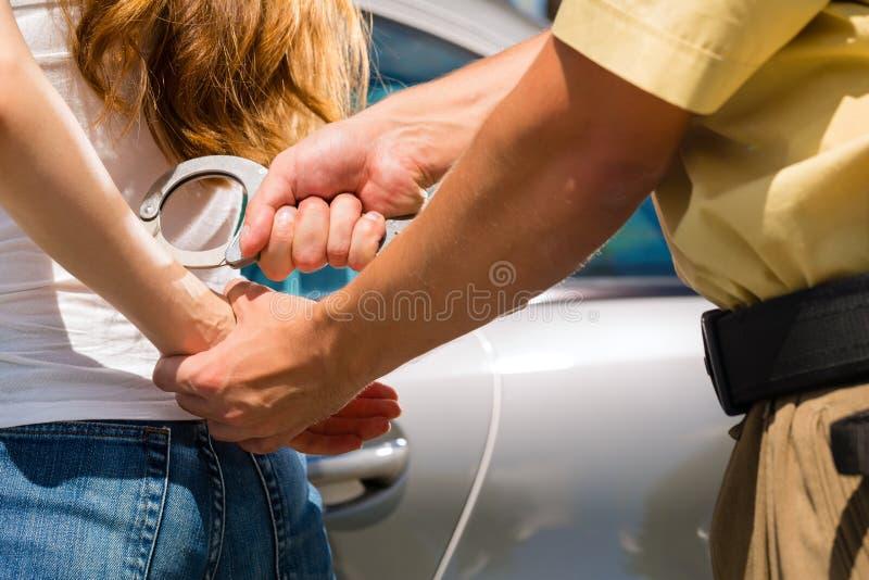 Oficial de policía que arresta a una mujer con las esposas imagen de archivo libre de regalías