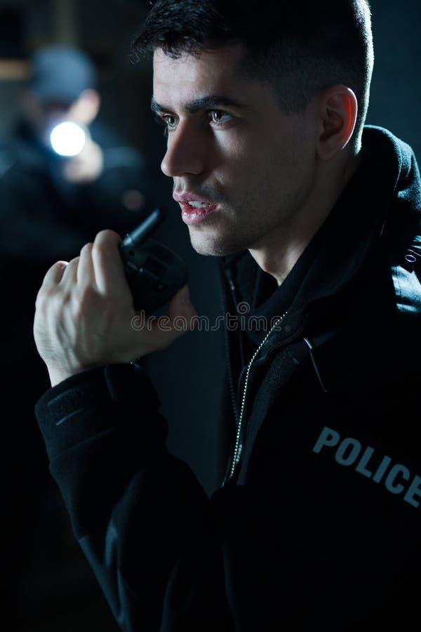 Oficial de policía que sostiene la radio fotografía de archivo libre de regalías