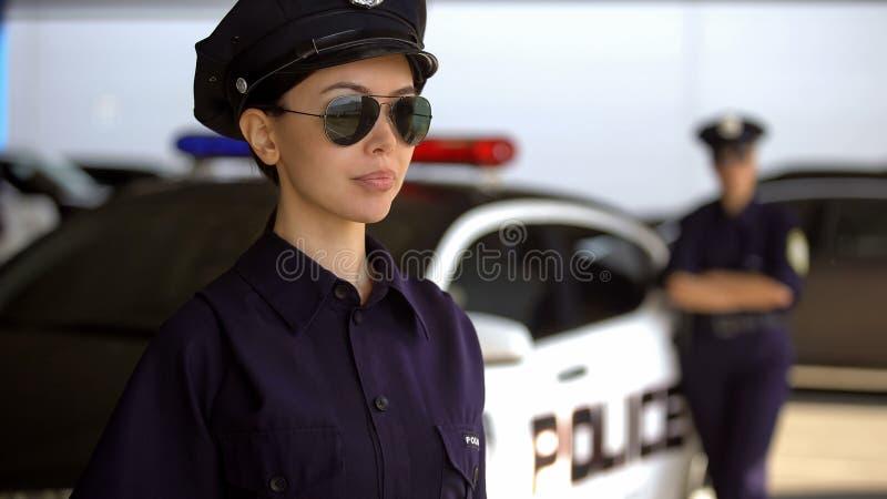 Oficial de policía serio que patrulla las calles, socio cerca del coche en el fondo, trabajo imagen de archivo libre de regalías