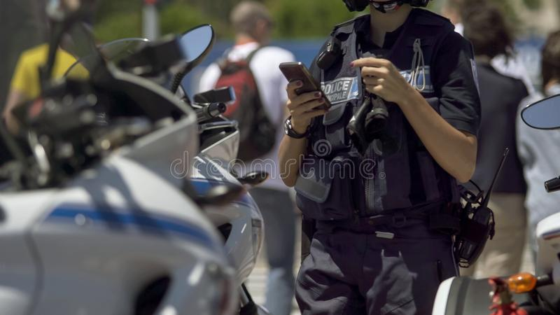 Oficial de policía de sexo femenino que se coloca al lado de la moto, comprobando el teléfono móvil de servicio fotografía de archivo libre de regalías