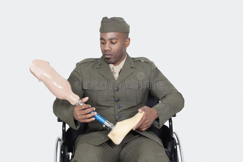 Oficial del ejército triste de los E.E.U.U. en la silla de ruedas que lleva a cabo el pie de la prótesis sobre fondo gris imagenes de archivo