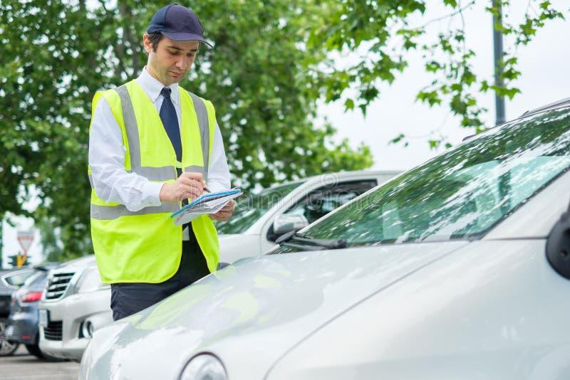 Oficial do estacionamento que escreve um bilhete para uma violação do estacionamento fotografia de stock
