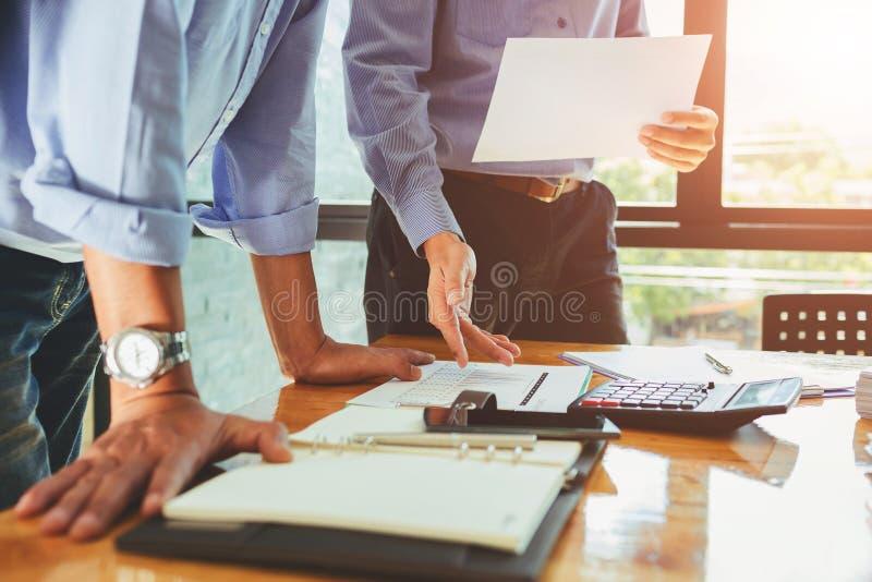 Oficial do negócio dos trabalhos de equipa que trabalha duramente investindo o repor financeiro imagens de stock