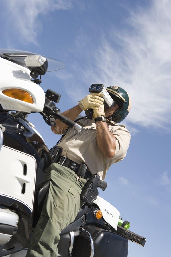 Oficial Sitting On Bike del tráfico y velocidad de la supervisión a través del arma del radar imagenes de archivo