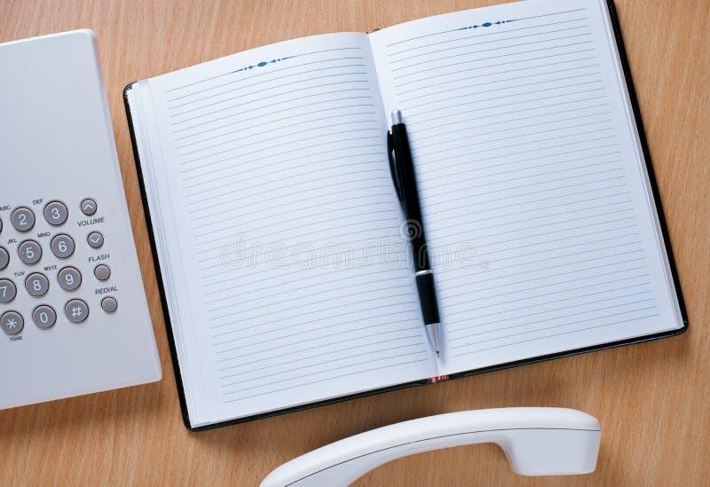 Oficial Work Area del teléfono con el cuaderno y la pluma fotos de archivo libres de regalías