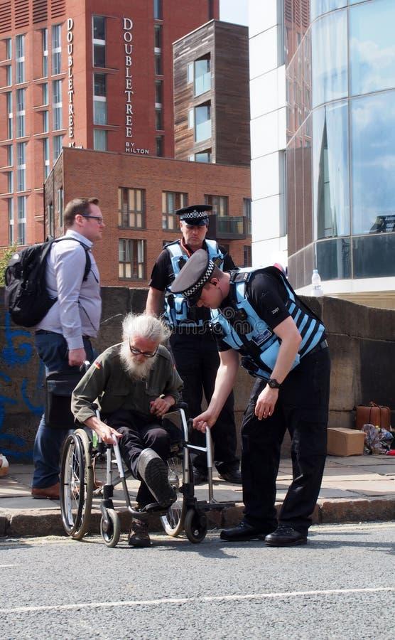 Oficiales de enlace de la policía que ayudan a un hombre en una silla de ruedas en la protesta de la rebelión de la extinción que fotos de archivo libres de regalías