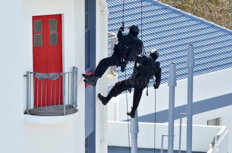 oficiales de policía del Contador-terrorismo abseiling un edificio imagenes de archivo